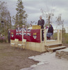Original title:  [Men and women seated on small stage behind John G. Diefenbaker speaking at podium during northern tour of Canada, Inuvik].