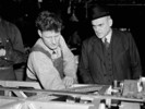 Original title:  Hon. C.D. Howe speaks with a workman at an aircraft factory.