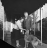 Original title:  Rt.Hon. John George Diefenbaker, Prime Minister of Canada, and Mrs. Olive Diefenbaker with pet dog on door step of official residence, 24 Sussex Drive.