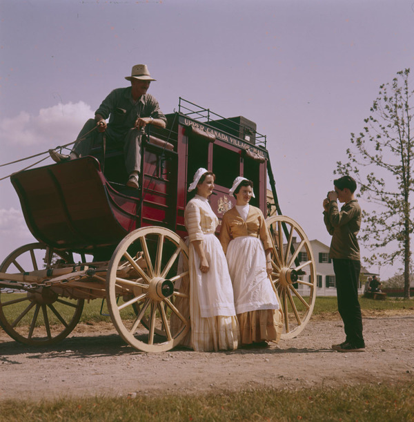 Original title:  MIKAN 4314222 Two dairy maids in costume of the late 1800's standing in front of a covered stage coach. Upper Canada Village.   septembre 1961 [206 KB, 1000 X 1018]