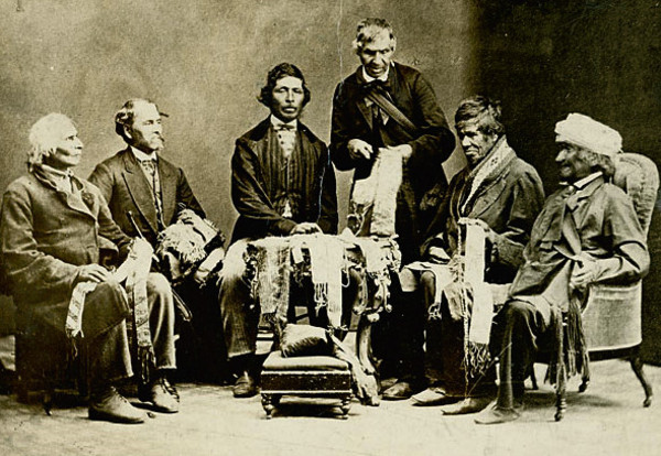 "Original title:    Description English: Chiefs of the Six Nations at Brantford, Canada, explaining their wampum belts to Horatio Hale September 14, 1871. Image shows Joseph Snow (Hahriron), Onondaga Chief;George H. M. Johnson (Deyonhehgon), Mohawk chief, Government interpreter and son of John Smoke Johnson; John Buck (Skanawatih), Onondaga chief, hereditary keeper of the wampum; John Smoke Johnson (Sakayenkwaraton), Mohawk chief, speaker of the council; Isaac Hill (Kawenenseronton), Onondaga chief, fire keeper; John Seneca Johnson (Kanonkeredawih), Seneca chief. Hale inscribed these photographs, which he sent to colleagues, ""The wampum belts were explained to me on the reserve, at the residence of Chief G. H. M. Johnson; and at my request the chiefs afterwards came with me to Brantford, where the original photograph . . . was taken.--H. Hale, Clinton, Ont."" This copy of the photographs was one tha"